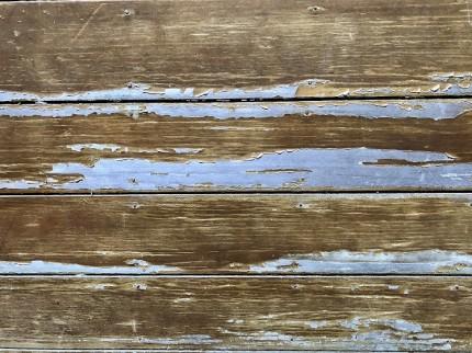 傷んだ木製玄関ドアの塗装面